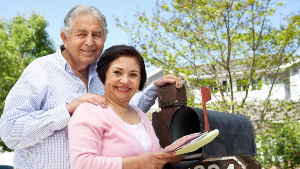 Senior Hispanic Couple Checking Mailbox For Card from their Doctor