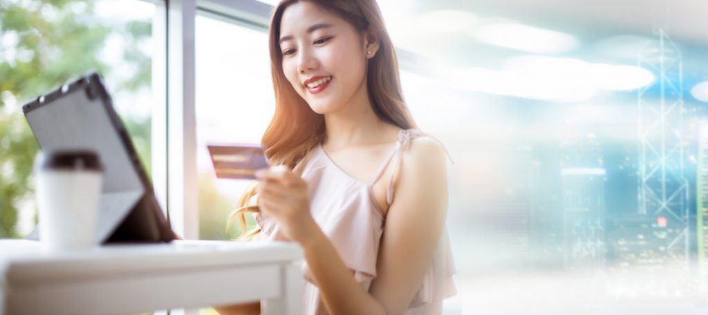 Asian woman paying bill online with credit card.